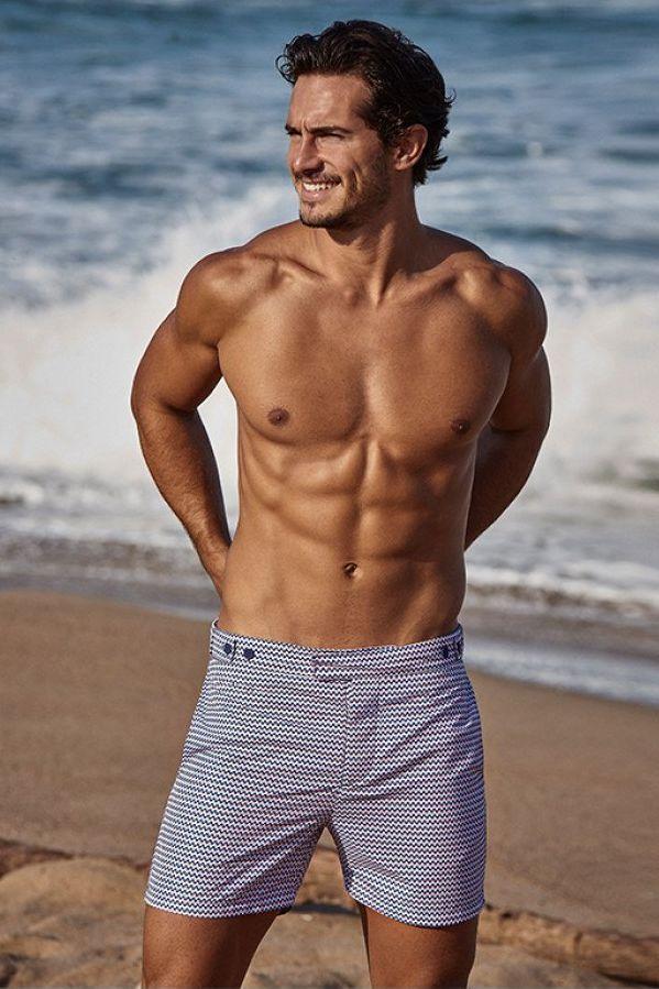 hombre en la playa con bañador azul
