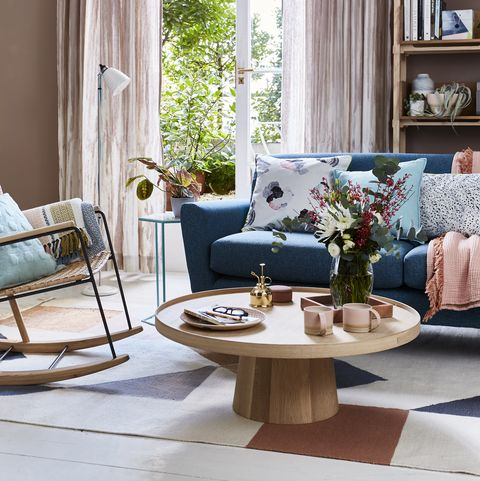 interior shot of a sitting room sofa and coffee tableliving room team a mid century style sofa with a pared back circularcoffee table for elegant simplicity lightweight full length curtains in aneutral colour bring softness and an airy feel to the room