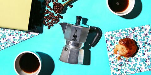 bialetti moka pot with coffee beans and pastry