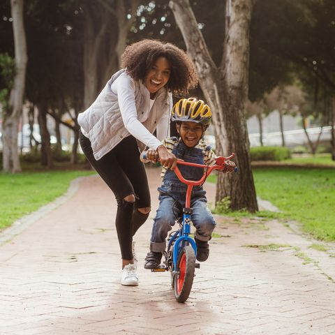 mom teaching her son biking at park