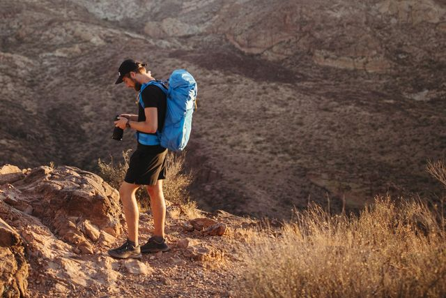 a man with a blue backpack in the desert