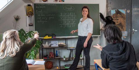 Twee volwassenen die in de schoolbanken zitten en een juf staat les te geven voor een bord