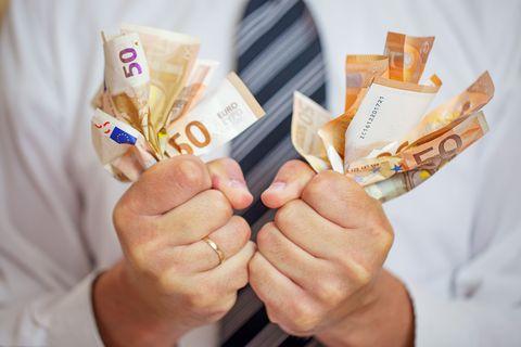 money addicted, greedy businessman squeezing money love of money
