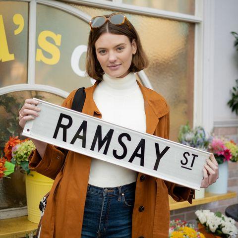 Монтана Кокс держит знак Рамзи-стрит, когда она присоединяется к Соседи в роли Бритни Барнс.