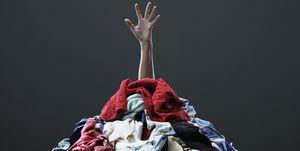 Mano saliendo de montaña de ropa