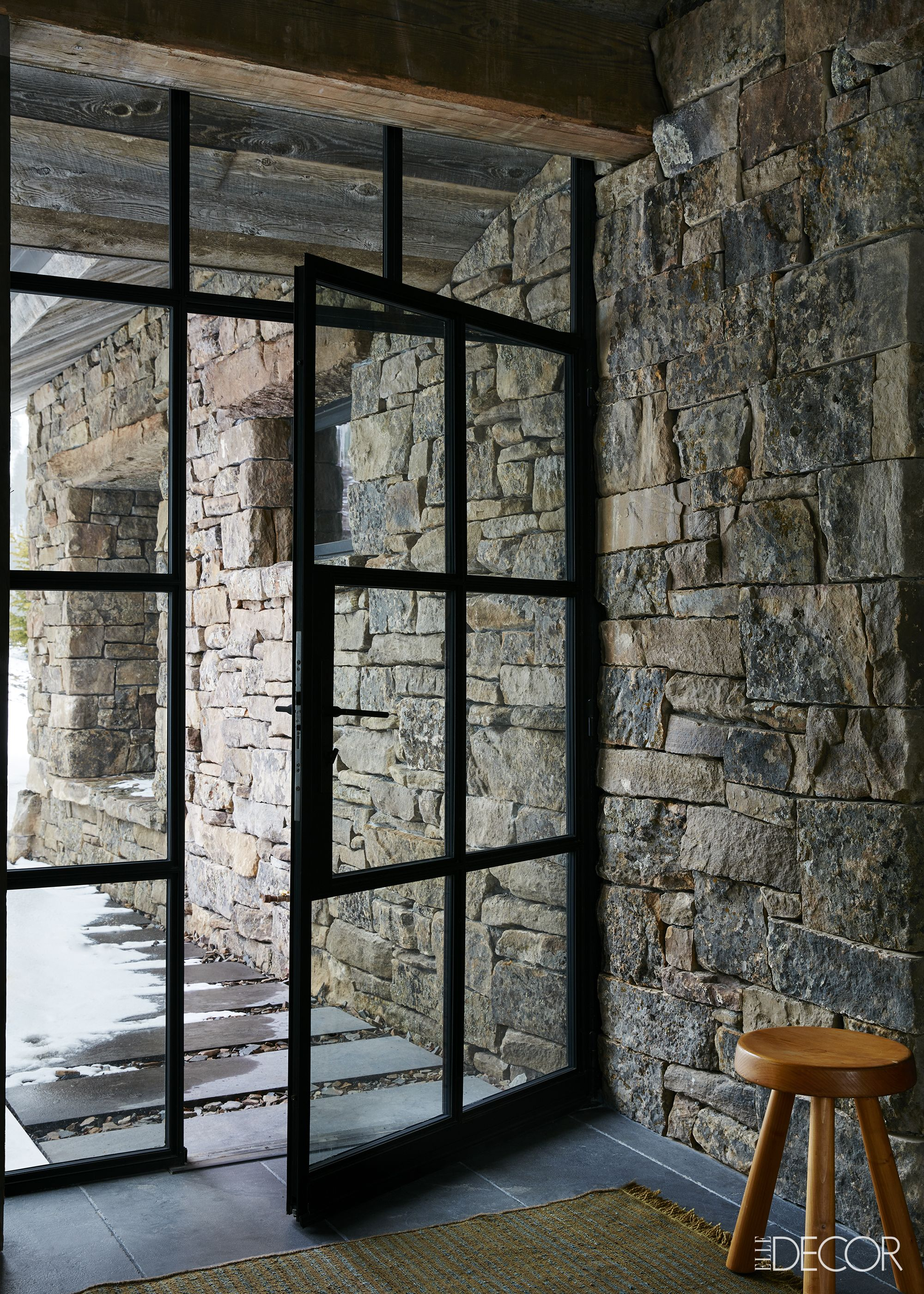 Black steel door to apres-ski room in stone Montana ski chalet on Hello Lovely