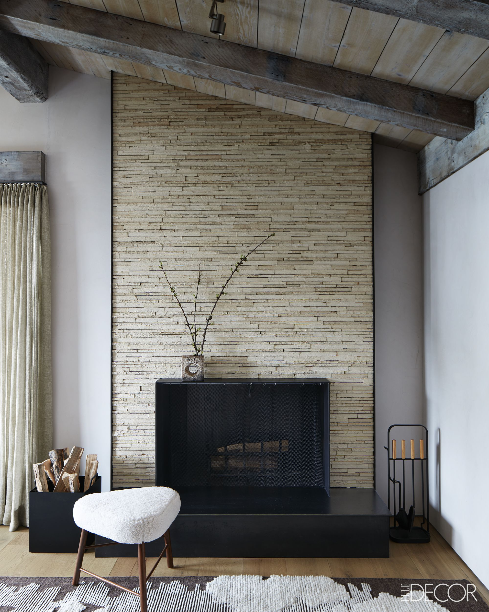 Black steel fireplace surround in rustic chic bedroom in ski chalet on Hello Lovely