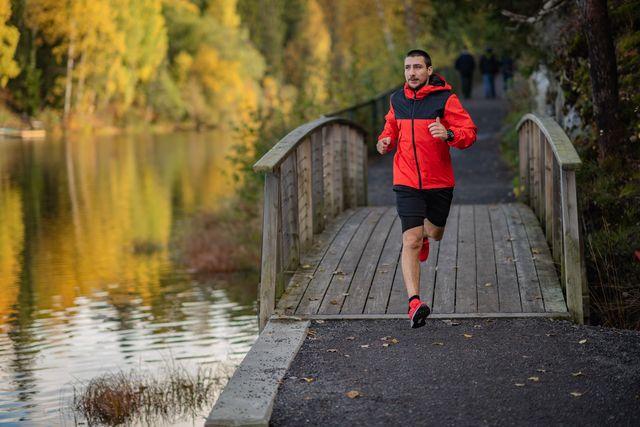 hombre corriendo al lado de un lago
