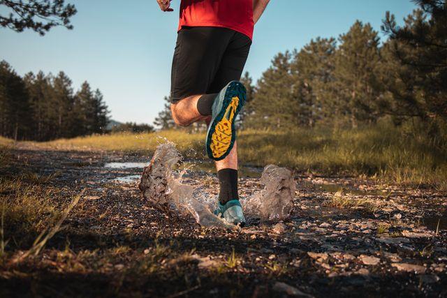 corredor corriendo sobre un charco de agua por la montaña morning jogging in a forest
