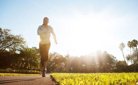 Female runner running at sunrise through a park