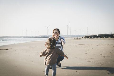 una joven con gafas se dispone a abrazar a su bebé en la arena de la playa