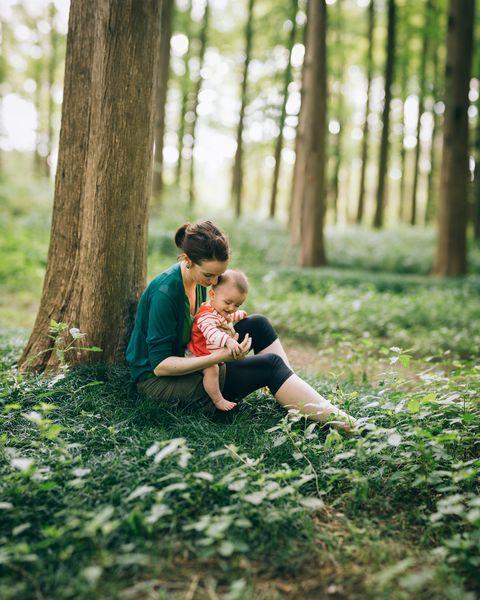 una mujer y su hijo sentados en el bosque