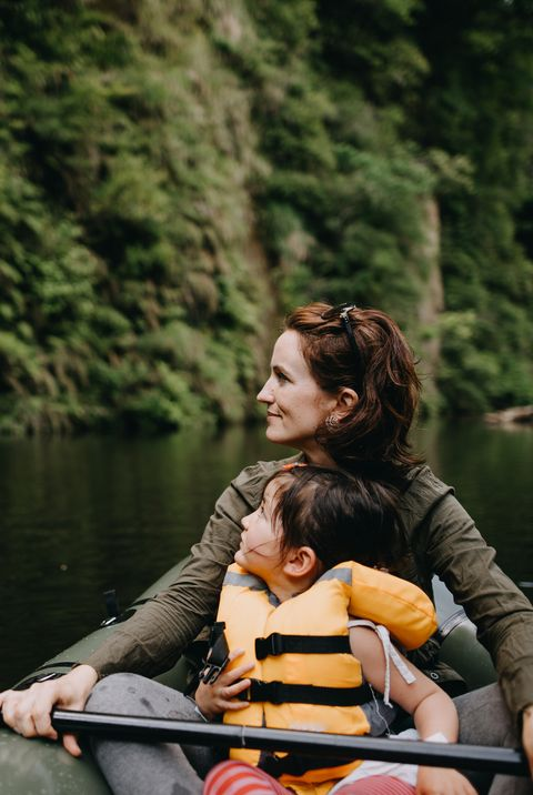Mother and child enjoying view from inflatable boat on river