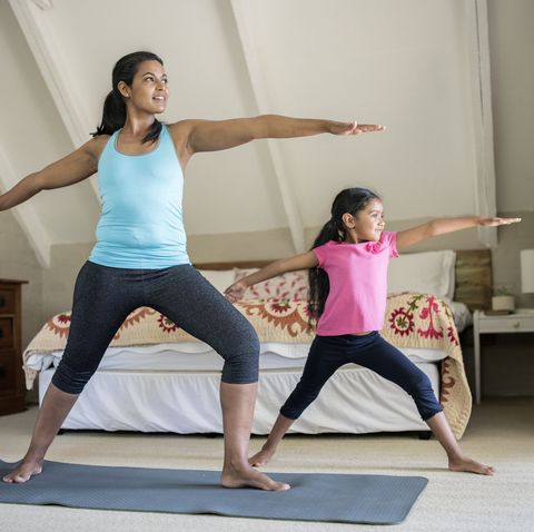 Mother and daughter practicing yoga in bedroom