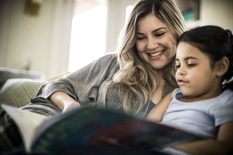 mother and daughter 7yrs reading book on couch