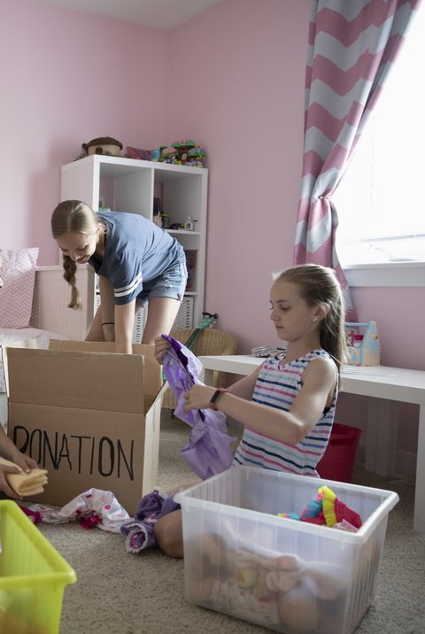 Mother and daughters organizing bedroom, donating