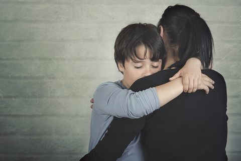 mother and son embracing against wall