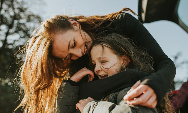 a mother bends down to embrace her daughter from behind