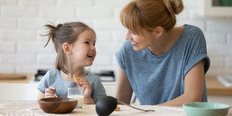 mother looking at little daughter and feeding after bake cookies