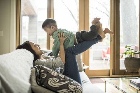 mother playing with young son 2 yrs on couch at home