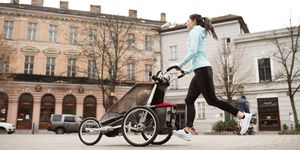 Mother running with child in stroller in the city
