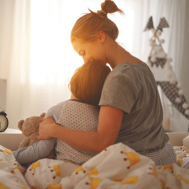 mother wakes her daughter in bed in  morning