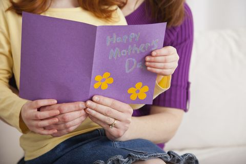 Mother with daughter (4-5) holding Mother's Day card together, midsection