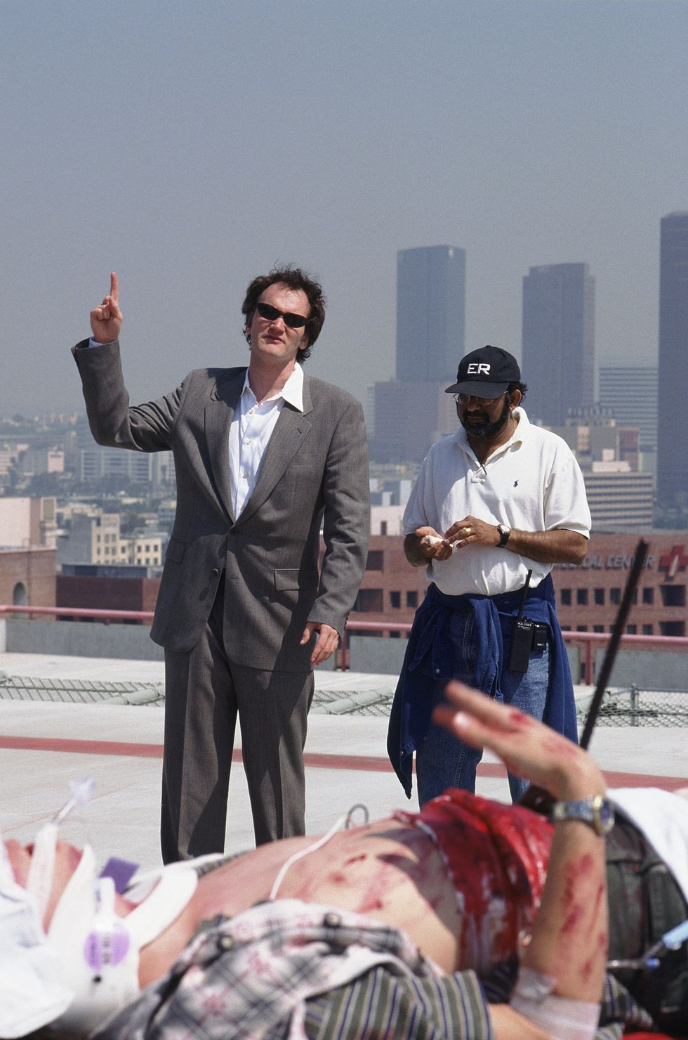 ER (1995) Tarantino gives direction on a rooftop on the set of ER. George Clooney reportedly asked for Tarantino to direct an episode of the show after he starred in the director's film, From Dusk Till Dawn.