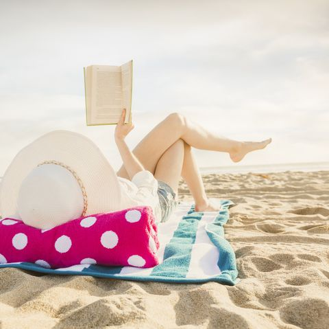woman laying on beach towel reading book