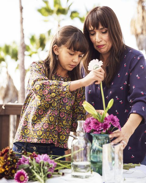 mother and daughter arranging flowers in a vase