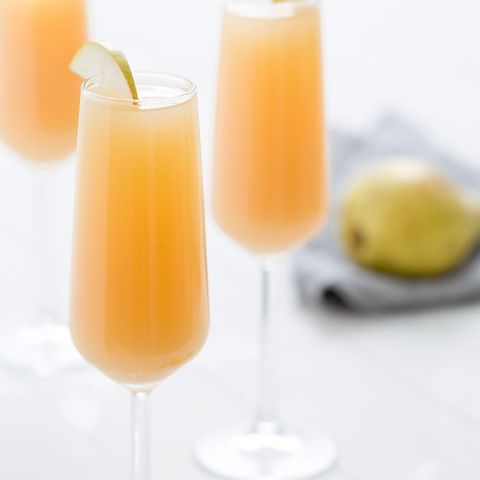 two champagne glasses filled with pear mimosas