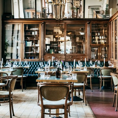 an empty luxurious restaurant with large wooden cabinets and leather seating