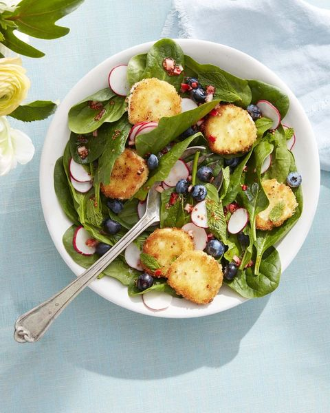 spinach and mint salad with crispy goat cheese in bowl.