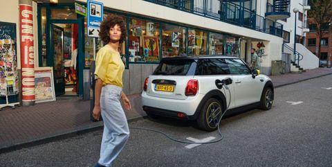 vrouw loopt op straat met mini cooper electric op achtergrond