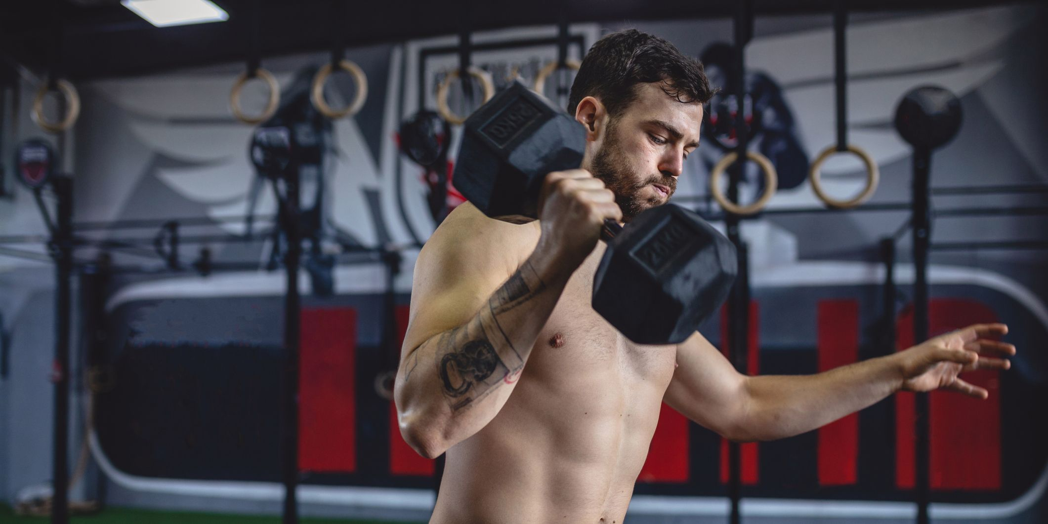 Motivated athlete exercising with dumbbells at a gym