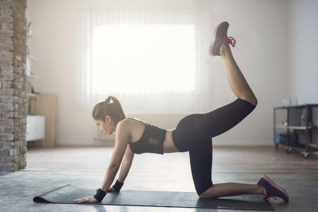 mujer haciendo ejercicio de glúteos en cuadrupedia