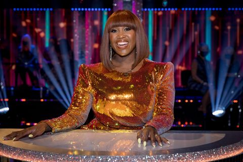 strictly come dancing judge motsi mabuse wearing an orange sequinned dress, sitting behind her desk