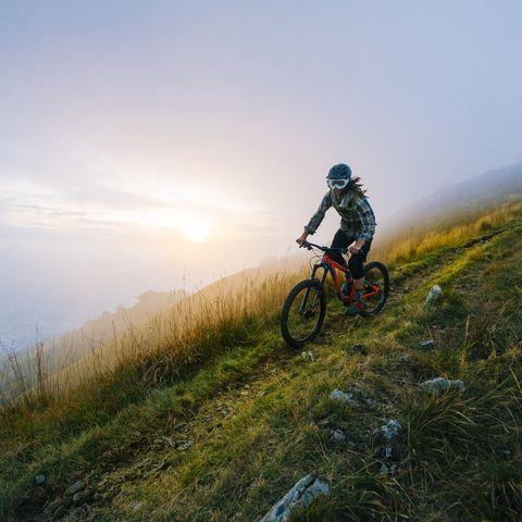 mountain biker traverses high mountain ridge, with dog