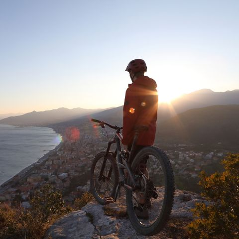 Mountain biker watches sun setting over distant mountains from hilltop