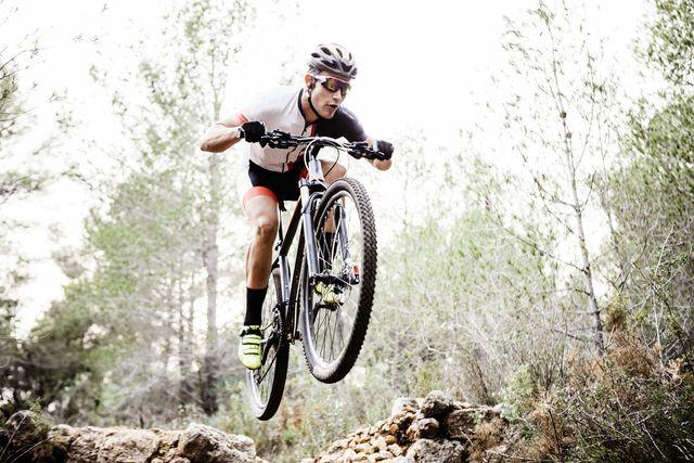 un ciclista pasa volando sobre las piedras del terreno durante una ruta en bicicleta de montaña