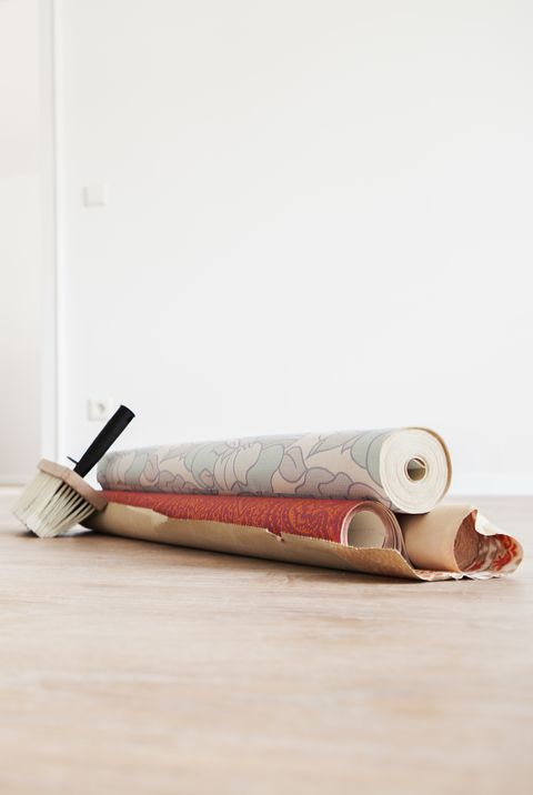 Moving house with rolls of wallpaper on wooden floor