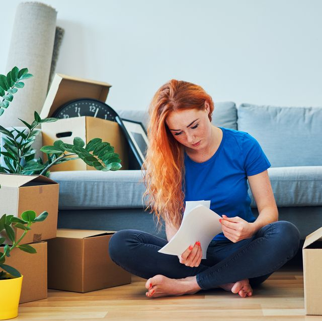 woman looking through apartment rent agreement after moving home