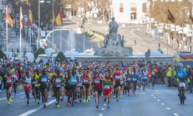 cientos de corredores pasan por delante de la fuente de la plaza de cibeles de madrid en el movistar media maratón de madrid