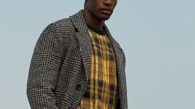 model wearing a yellow sweater and grey overcoat