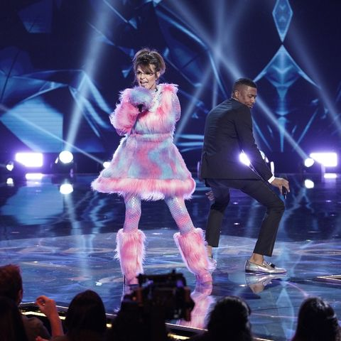 Sarah Palin, in a baby pink and blue costume, sings on stage as host Nick Cannon dances behind her.