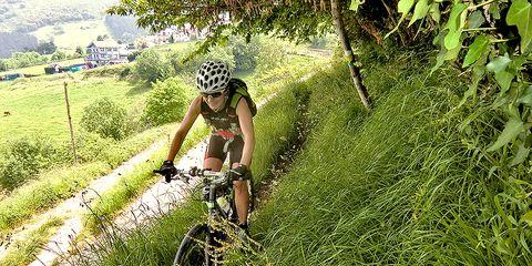 cyclist riding through skinny singletrack in tall grass
