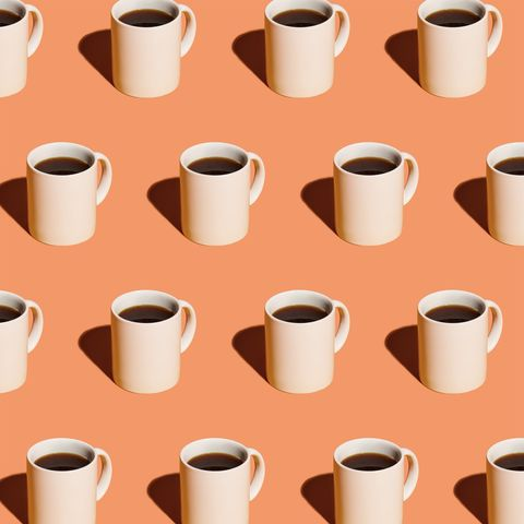 Mugs of black coffee in rows against peach background