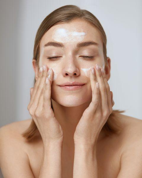 una mujer limpia su rostro con un producto en el espuma