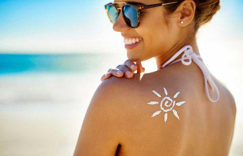 Mujer modelo sonriendo en la playacon protección solar con forma de sol en la espalda