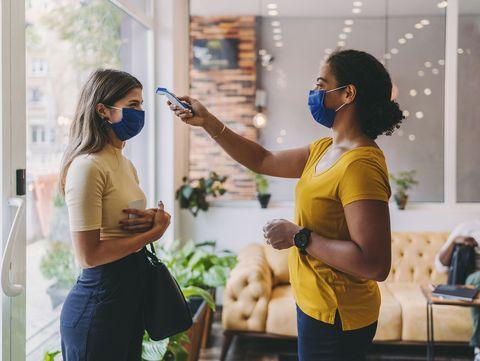 una mujer toma la temperatura a una chica antes de entrar en un local